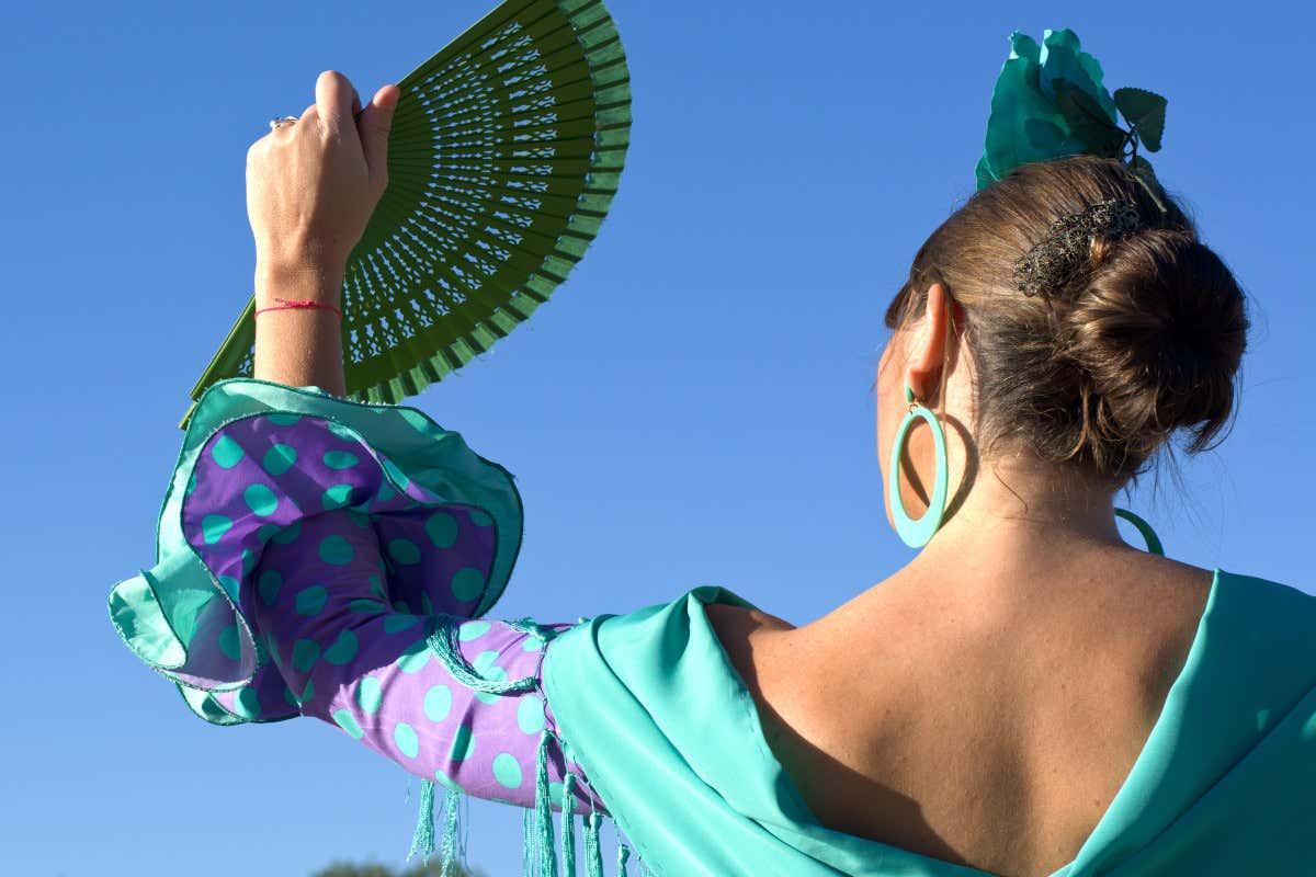 Vista de medio cuerpo superior de una mujer vestida con un traje de flamenca y ondeando un abanico frente a un cielo azul despejado.