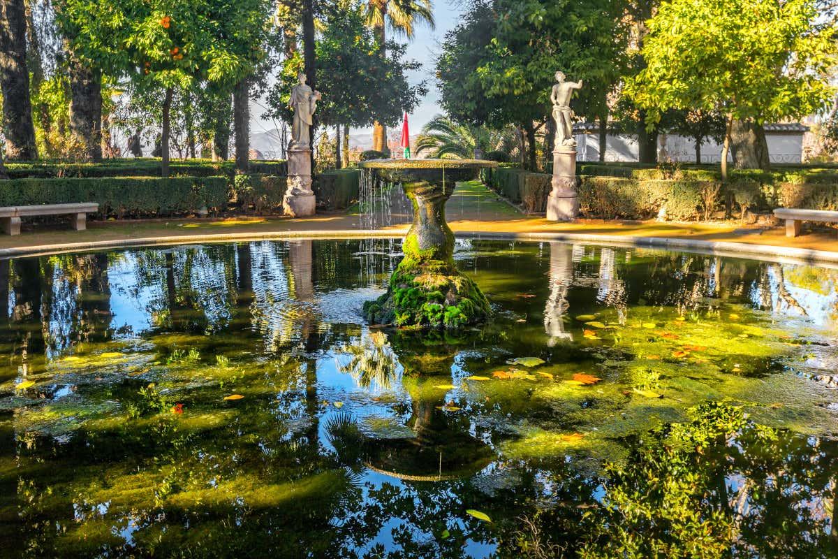 Una enorme fuente repleta de vegetación frente a dos esculturas humanas en unos jardines del Carmen de los Mártires, en Granada.