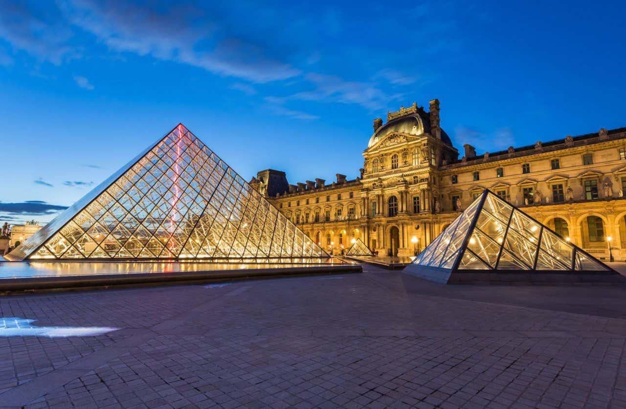 Famosa entrada del Museo del Louvre con las pirámides de cristal en la noche de París