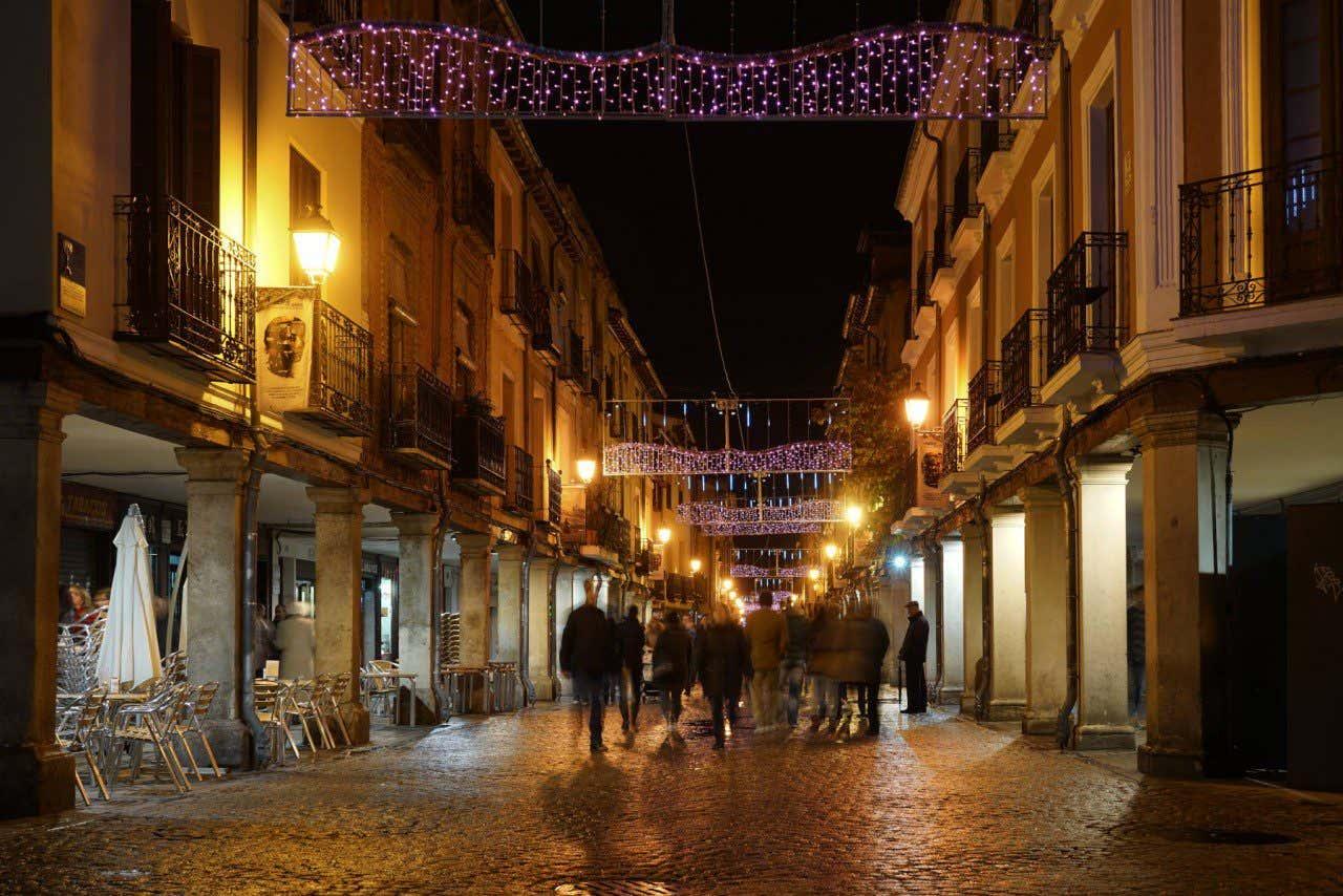 Calle Mayor de Alcalá con los típicos soportales de noche iluminada por las farolas