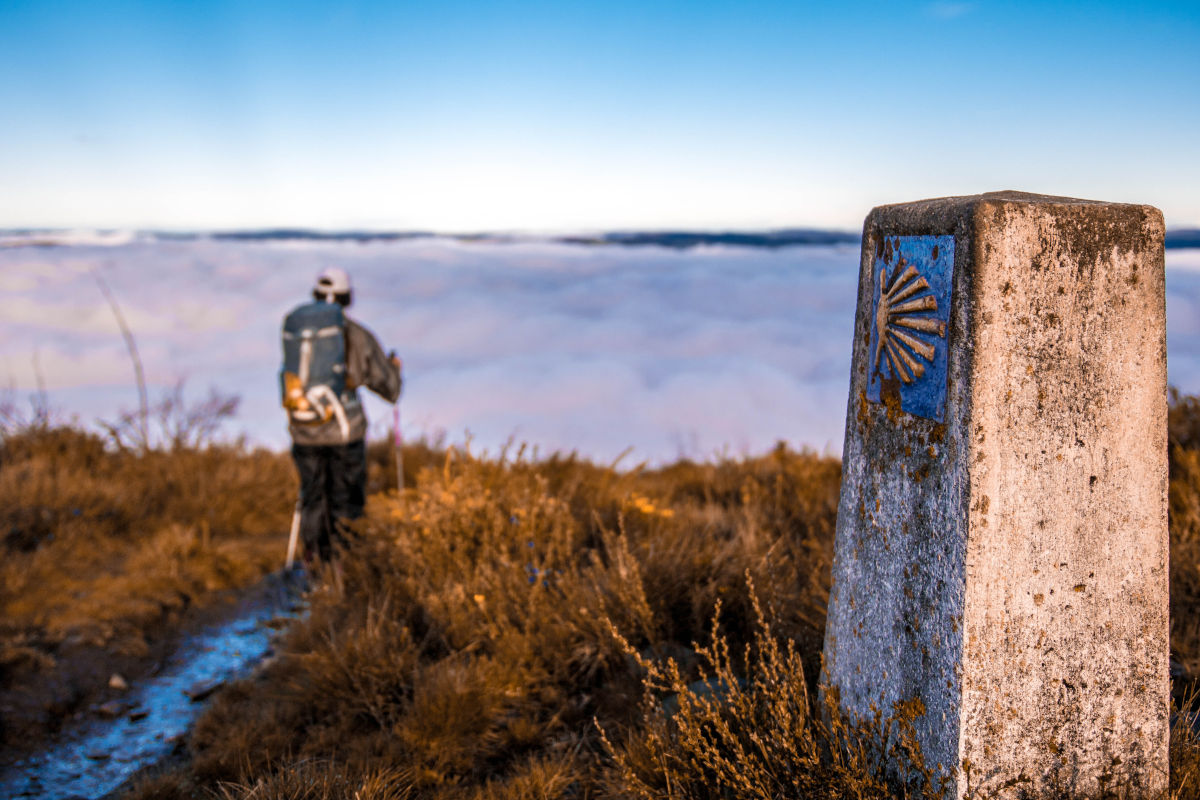 Un hombre caminando por un sendero asturiano frente a un mar de nubes y junto a un cartel identificativo del Camino de Santiago.