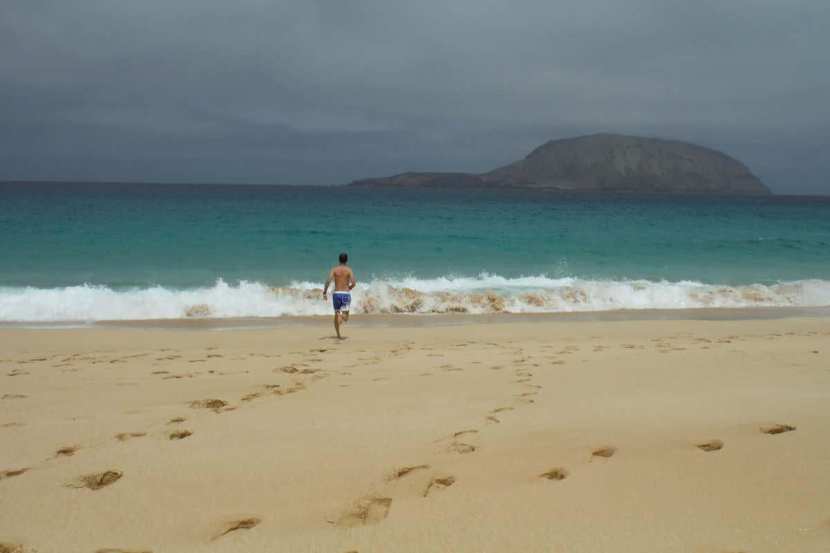 Aguas turquesas, arena dorada y David Chaves corriendo hacia el agua en la isla de La Graciosa.