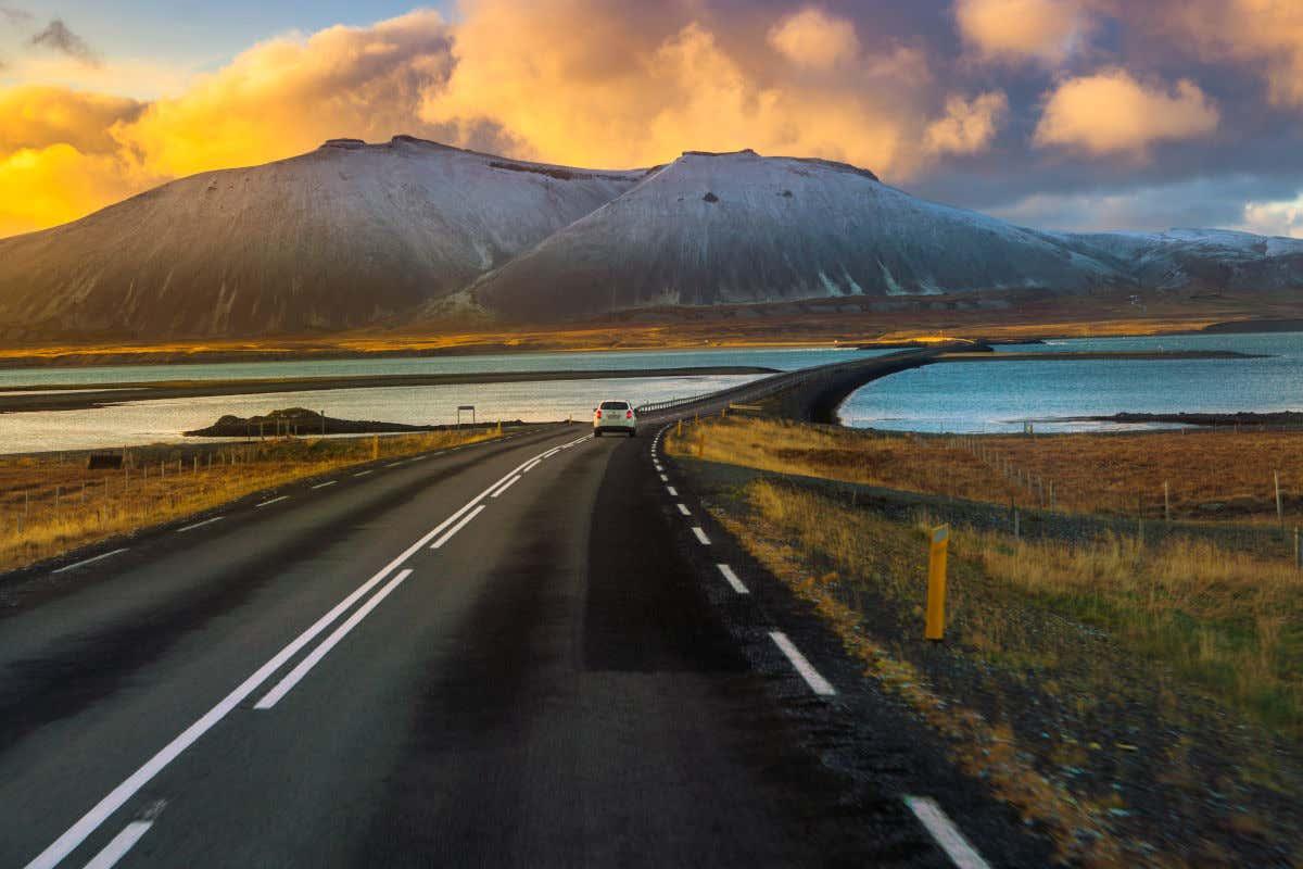 Un coche circula hacia adelante por la la carretera Ring Road de Islandia. En sus alrededores se pueden ver lagos de aguas cristalinas y altas montañas.