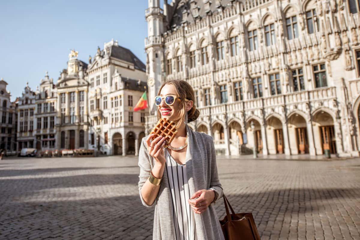 Una joven con gafas de sol y ropa de entretiempo disfrutando de un gofre en la Gran Place de Bruselas, frente al Ayuntamiento de la ciudad.