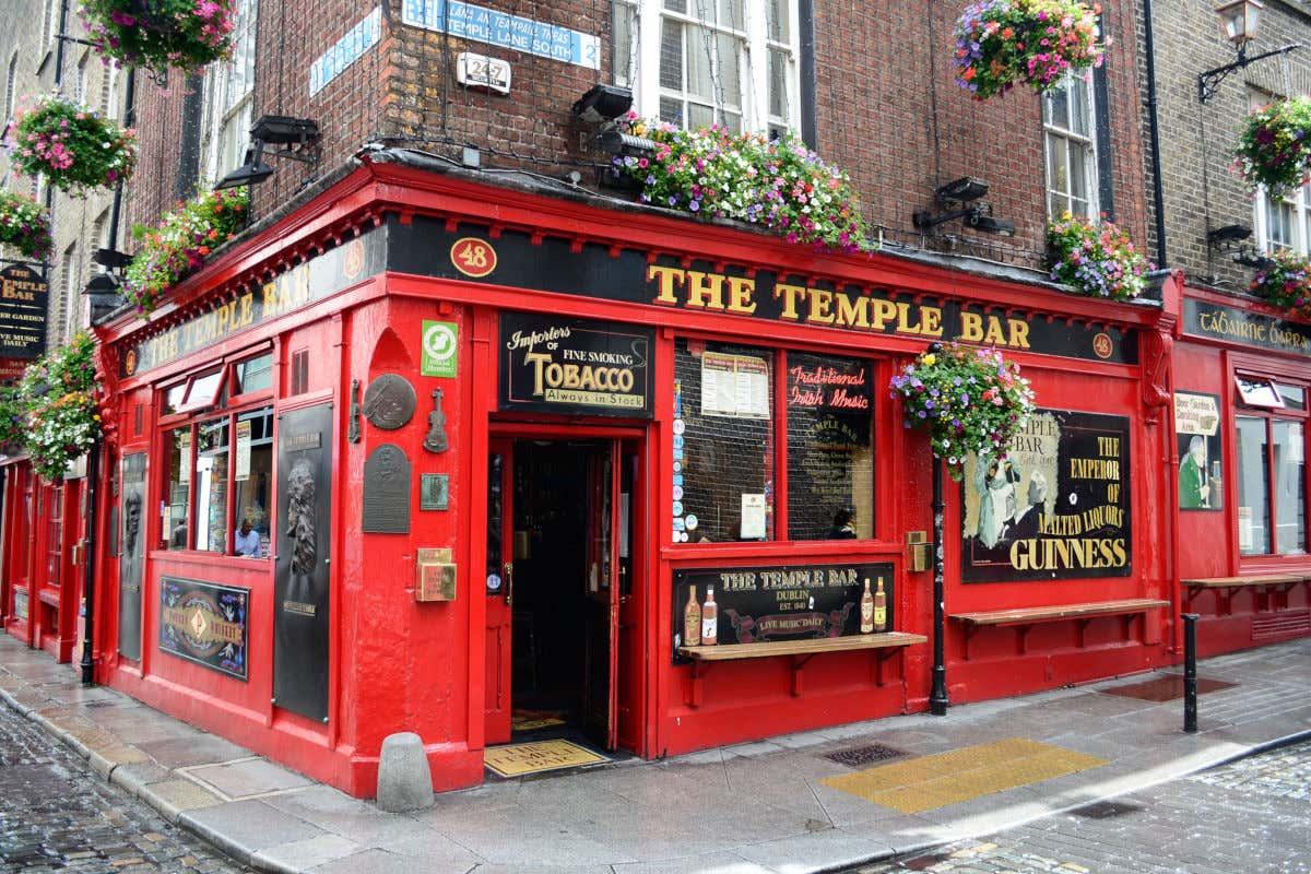 Fachada roja con decoración floral del pub irlandés The Temple Bar, uno de los más famosos del centro de Dublín.
