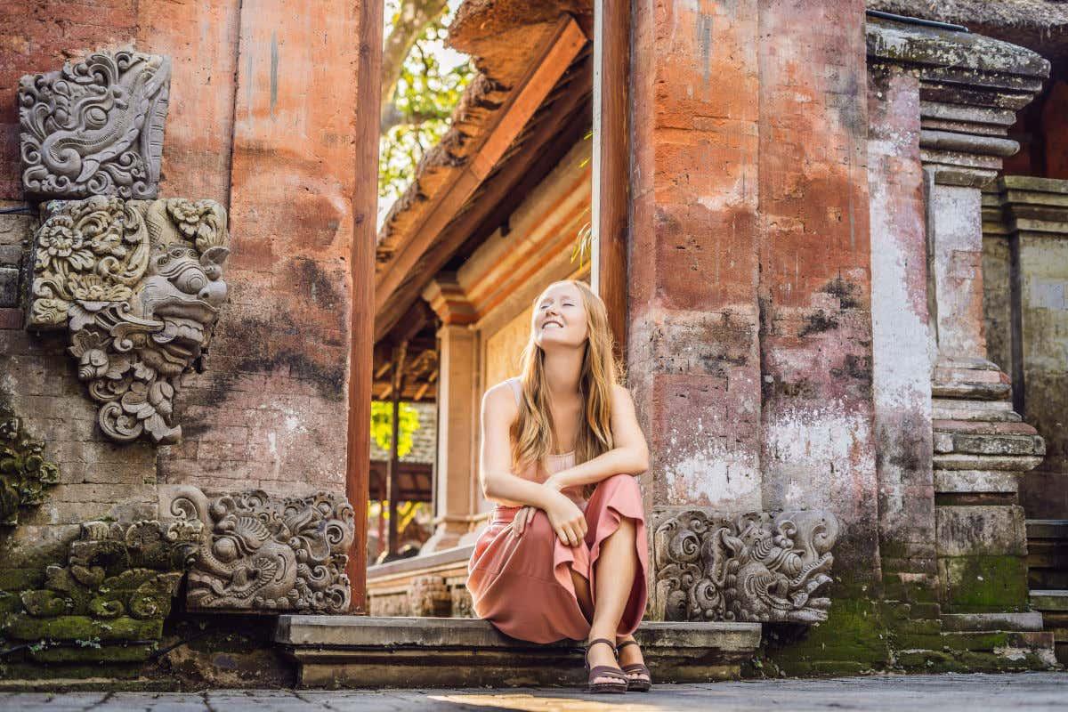 Una joven sentada en el templo Ubud, en Bali. Se aprecia una de las puertas del templo con varios relieves.