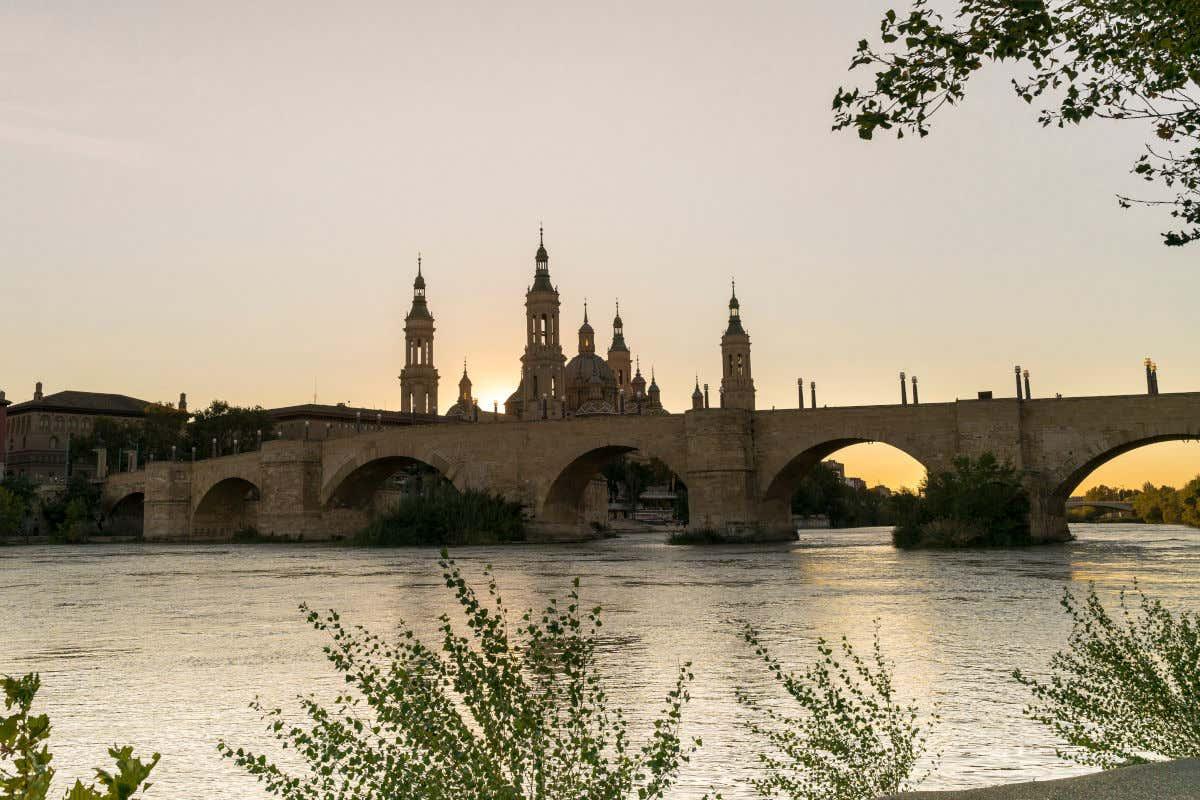 Río Ebro y puente de Piedra de Zaragoza al atardecer con la basílica de Nuestra Señora del Pilar al fondo.