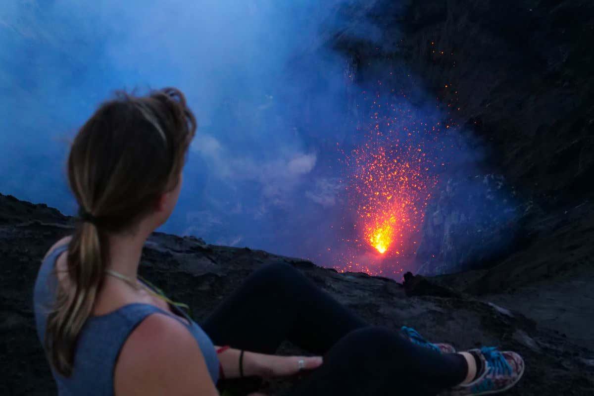 Una mujer con ropa deportiva sentada de espaldas mirando cómo brota la lava del cráter del Monte Yasur, en Vanuatu.