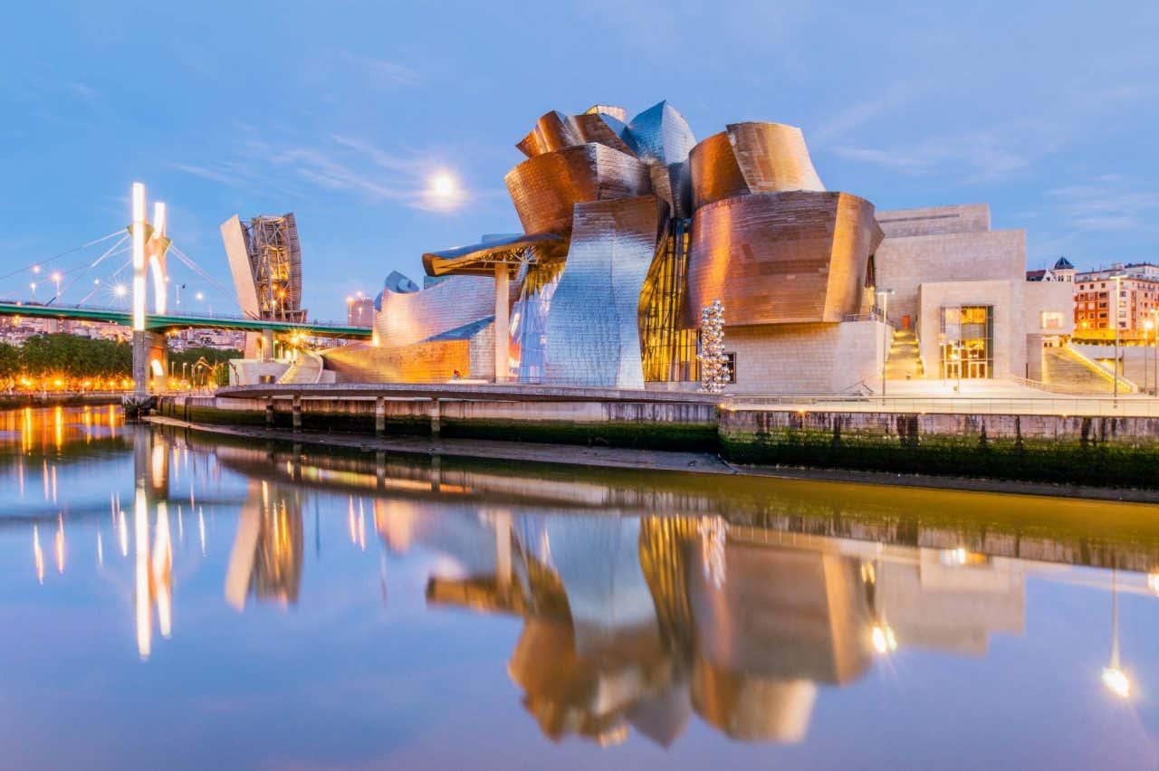 Vista del Museo Guggenheim en Bilbao al atardecer a la orilla de la ría