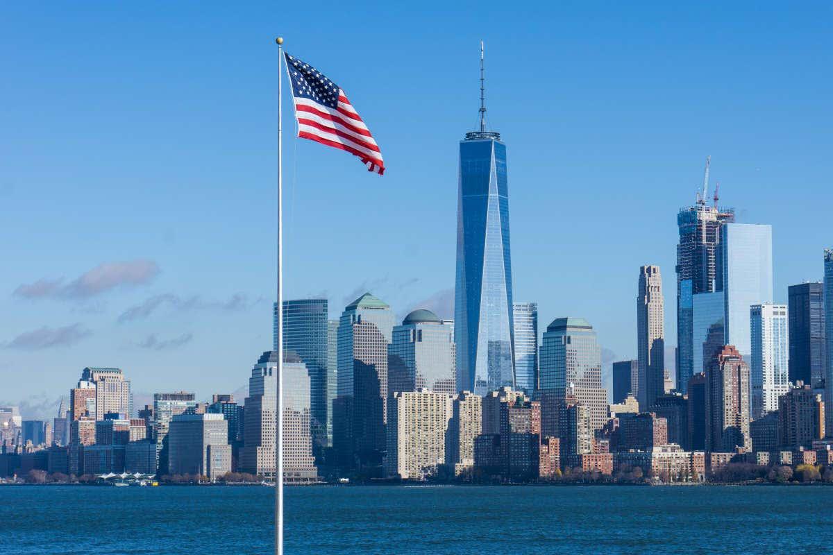 Panorámica de Nueva York con bandera y rascacielos detrás