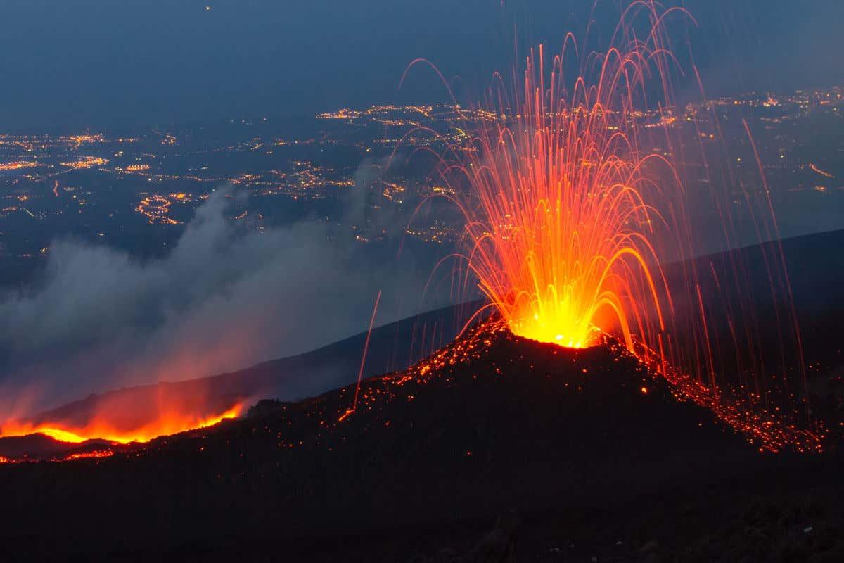 Vista nocturna del monte Etna en erupción expulsando gran cantidad de lava cerca de Catania.