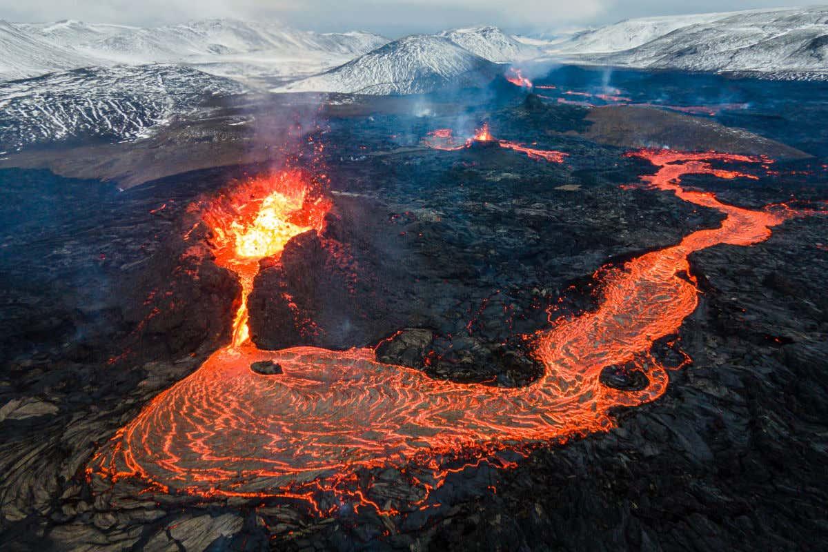 Montañas nevadas junto al volcán Fagradalsfjall de Islandia, mientras la lava fluye a través de su cráter y por los alrededores.