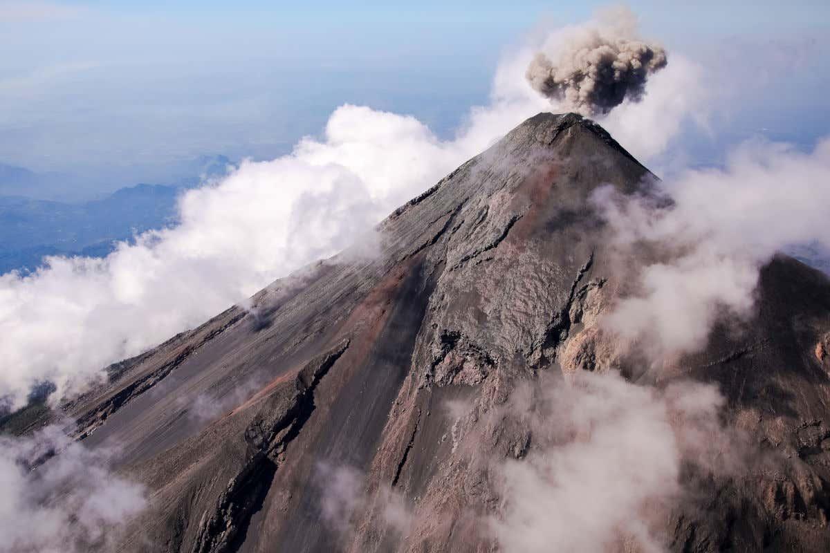 Cima del Volcán de Fuego emitiendo nubes de gases y humo en Guatemala.