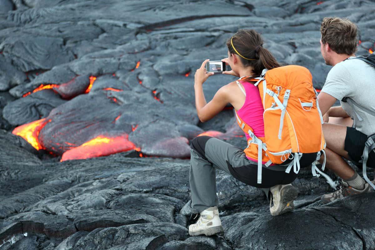 Dos turistas de espaldas con ropa deportiva haciendo fotografías con su móvil a las coladas de lava del Kīlauea, en Hawaii.