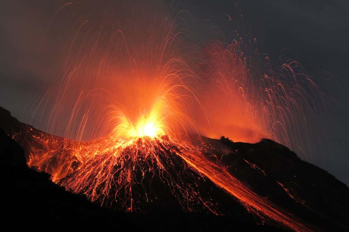 Imagen del volcán Estrómboli entrando en erupción emitiendo lava por la noche.