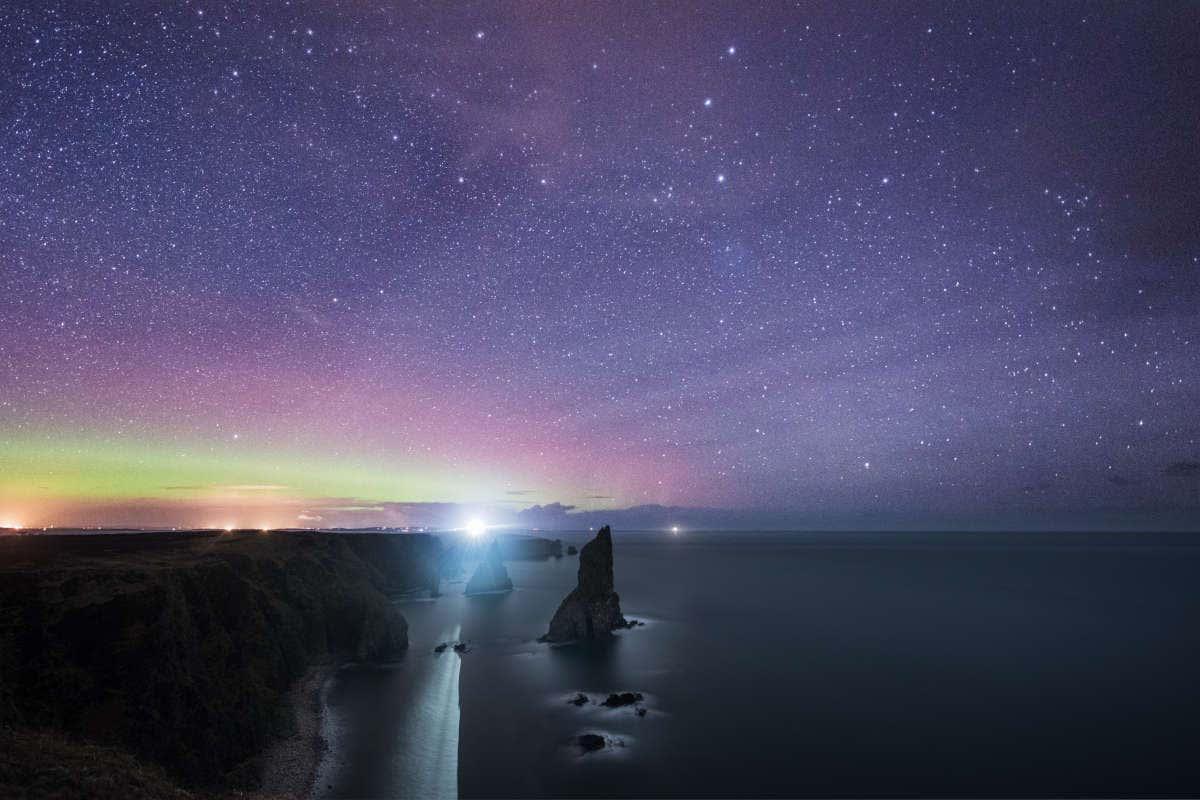 Paisaje escocés bajo el cielo estrellado en tonos morados