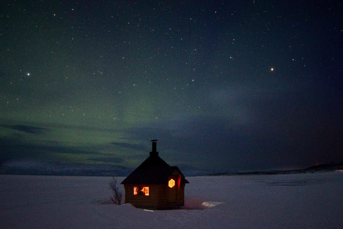Una casa en el paisaje helado de Kiruna bajo la aurora boreal