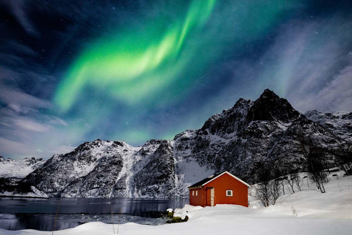 Una casa roja junto a las montañas de Svolvær bajo la aurora boreal