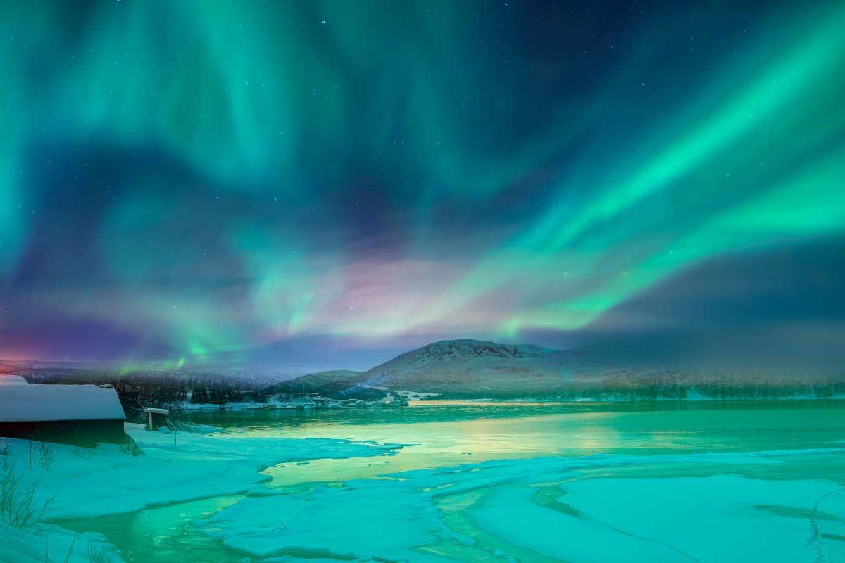Luces verdes, azules y rosas de la aurora boreal sobre el paisaje helado de Tromsø